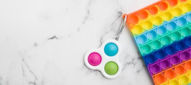 Fragmentar brinquedos sensoriais antistress da moda coloridos fidget push pop it e simle dimle no fundo de mármore com espaço de cópia