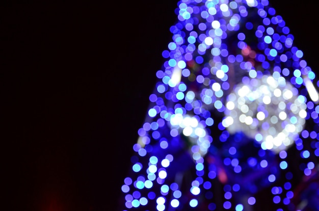 Fragmento borrado da árvore do ano novo. muitas luzes redondas em azul