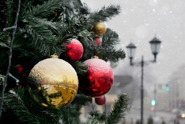 Fragmento da árvore de natal decorada com bolas vermelhas e amarelas levemente cobertas de neve ao ar livre no fundo desfocado da lanterna e edifícios.