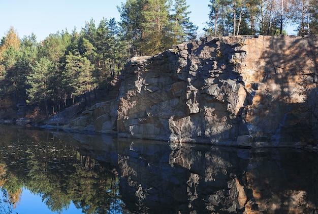 Fragmento da margem do lago com uma pedra na floresta de outono no início da manhã