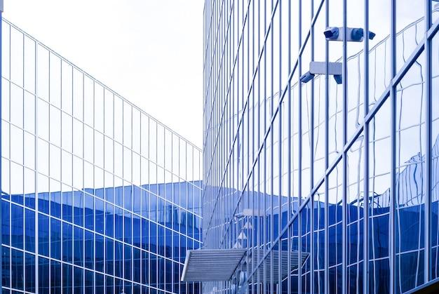 Fragmento de arquitetura urbana de alta tecnologia de fachadas de vidro e metal com câmeras de vigilância