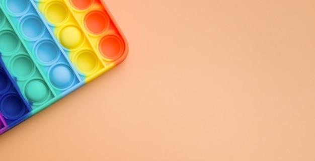 Fragmento de brinquedos sensoriais antistress na moda coloridos fidget push pop em fundo laranja