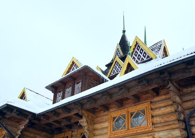Fragmento de casa de madeira com neve no telhado.