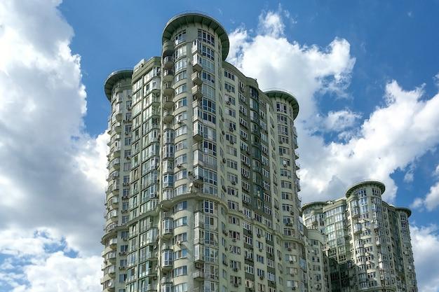 Fragmento de edifício residencial exterior moderno, alto, com muitas janelas.