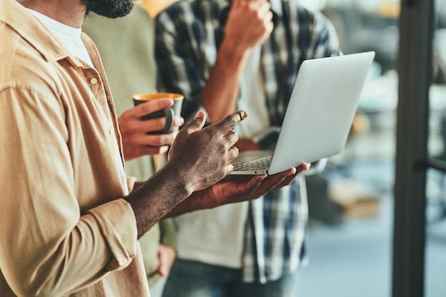 Fragmento de foto de dois homens olhando para a tela do laptop
