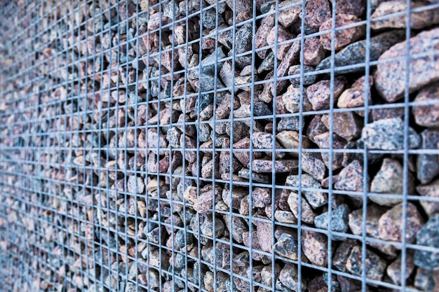 Fragmento de fundo de uma parede decorativa de uma pedra de granito e uma treliça de metal