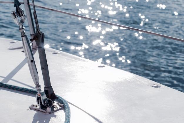 Fragmento de iate de fundo do casco de um veleiro com cordame contra o pano de fundo da água