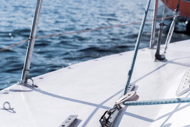 Fragmento de iate do casco de um veleiro com cordame contra o pano de fundo da água