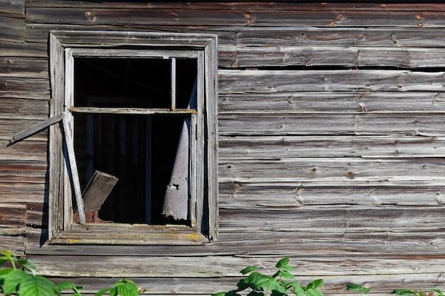 Fragmento de parede com janela de casa de madeira rústica abandonada. elemento de design espaço de cópia