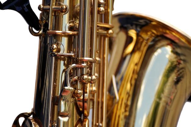 Fragmento de saxofone em fundo branco. sax de perto. perto do saxofone de chaves. instrumento maravilhoso.