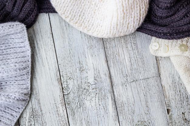 Fragmento de tricô roupas na mesa de madeira branca