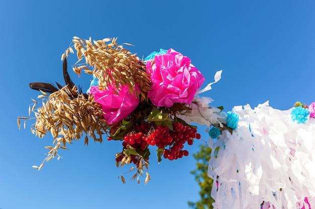 Fragmento de um casamento criativo, a árvore do casamento é decorada com viburnum, espigas de trigo, penas e flores de papel. tradições do casamento da ucrânia ocidental.