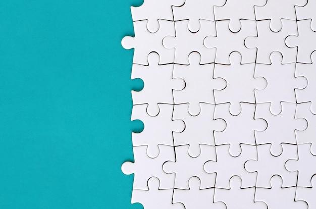 Fragmento de um enigma de serra de vaivém branco dobrado na superfície plástica azul.