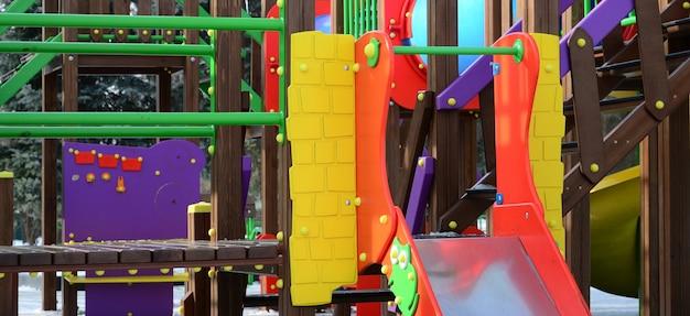 Fragmento de um parque infantil de plástico e madeira, pintado em cores diferentes