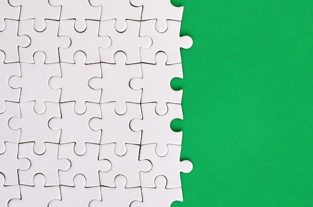 Fragmento de um quebra-cabeça branca dobrada no fundo de uma superfície de plástico verde