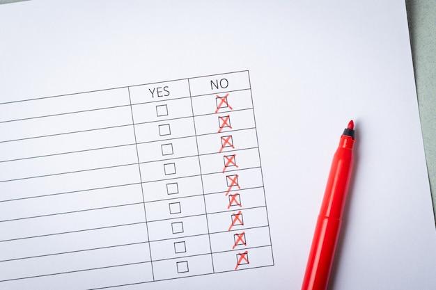 Fragmento de um questionário preenchido e um marcador vermelho em um fundo cinza