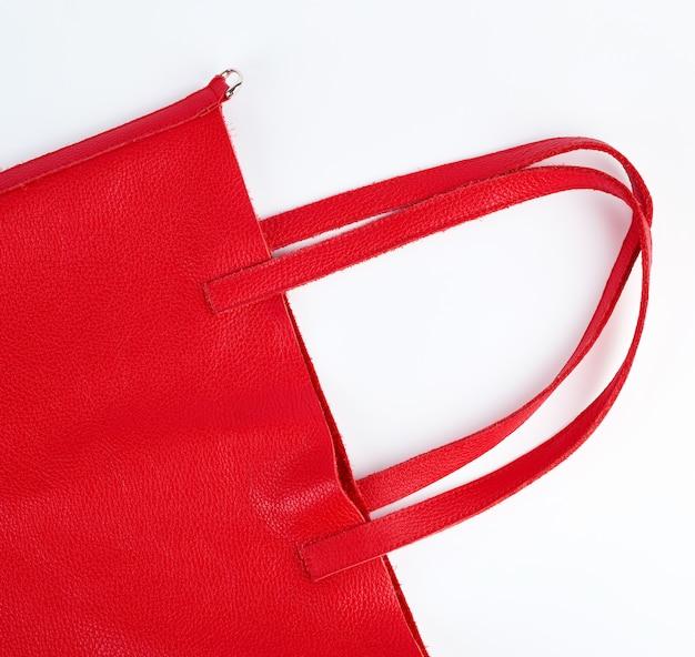 Fragmento de um saco de couro vermelho com alças em um branco