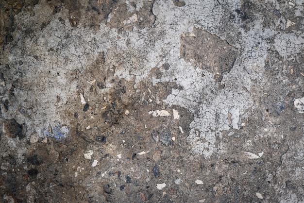 Fragmento de uma antiga muralha de cimento cinza com pedras negras