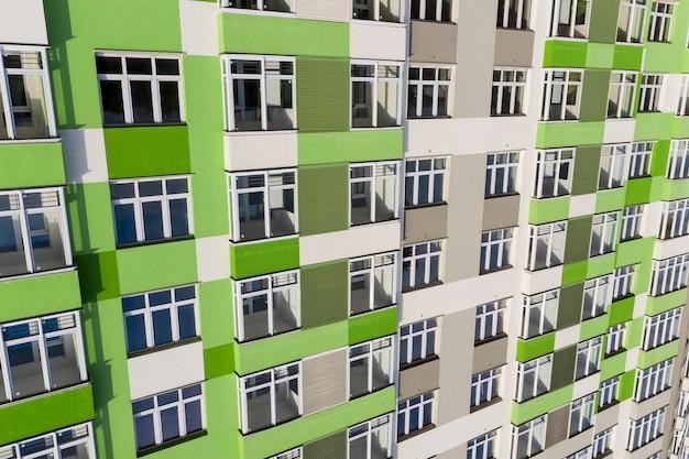 Fragmento de uma casa com uma nova fachada cinza-esverdeada moderna com janelas