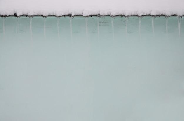 Fragmento de uma casa de apartamento com um monte de gelo pendurado sob o telhado