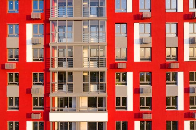 Fragmento de uma fachada vermelha moderna com janelas
