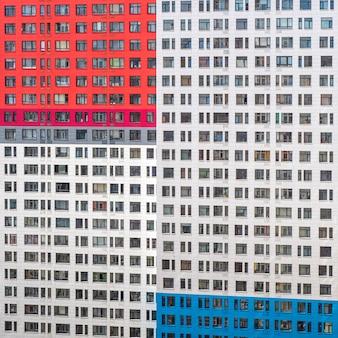 Fragmento de uma parede com janelas de um prédio de apartamentos de vários andares.