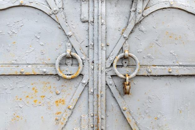 Fragmento de uma porta ou portão de metal velho cinza fechado com aldravas redondas e um cadeado enferrujado.