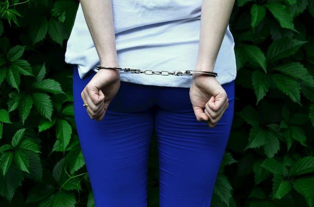 Fragmento do corpo de uma jovem criminosa com as mãos algemadas