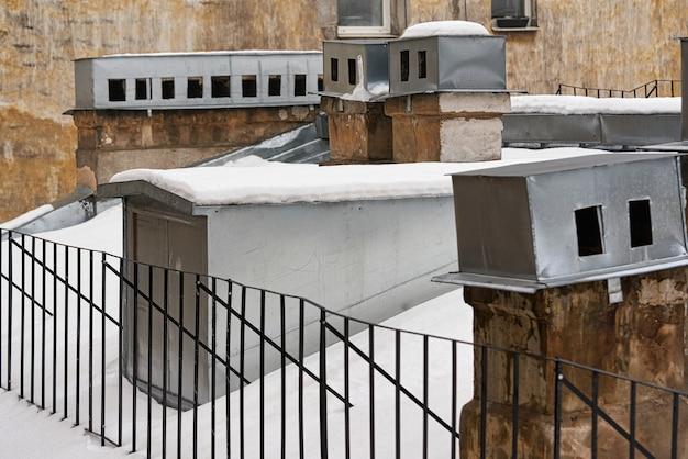 Fragmento do telhado de uma casa antiga com chaminés de tijolos