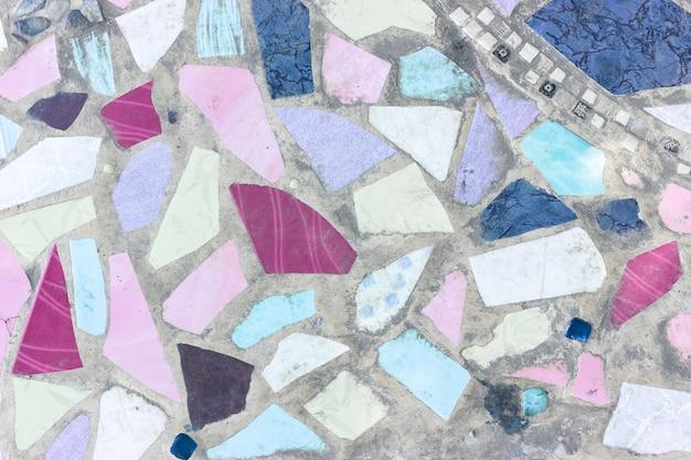 Fragmentos de cerâmica coloridos e piso de cimento