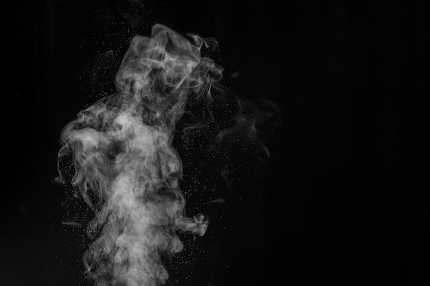 Fragmentos de fumaça em um fundo preto.