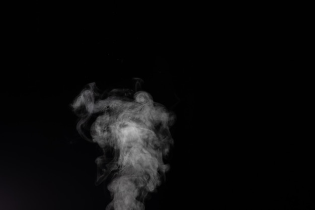 Fragmentos de fumaça em um fundo preto. Foto Premium