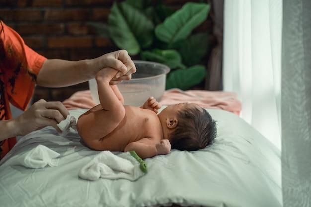 Fralda de bebê menina asiática substituída por uma mãe