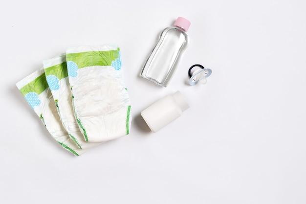 Fralda de mercadorias para bebês, talco de bebê, creme, xampu, óleo em fundo branco com espaço de cópia. vista superior ou configuração plana. conceito de maternidade