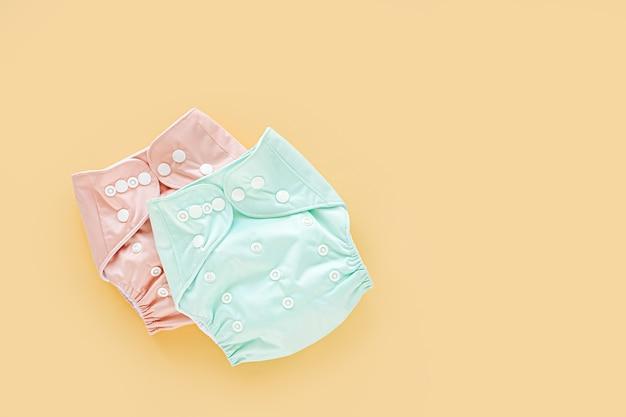 Fraldas de bebê de pano reutilizáveis. fraldas de pano ecológicas sobre um fundo amarelo. estilo de vida sustentável. conceito de desperdício zero.