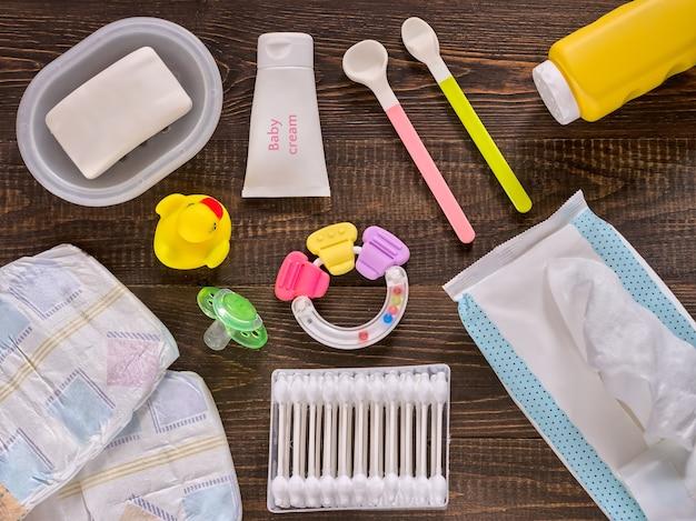 Fraldas japonesas, lenços umedecidos, sabonete, talco de bebê, creme, dizimista, cotonetes, colheres, chupeta e patinho em fundo de madeira