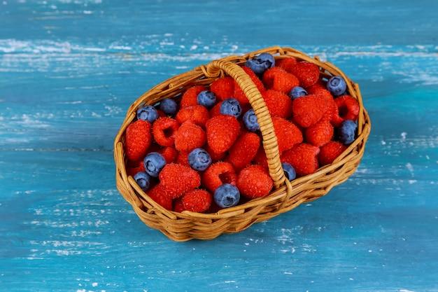 Framboesa com mirtilo na cesta em uma velha placa azul