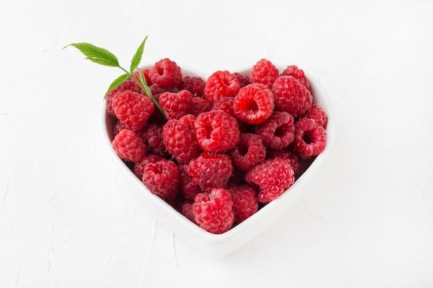 Framboesa em um prato de coração em uma vista superior branca