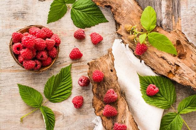 Framboesa em uma tigela, frutas e folhas em uma madeira gasto. vista do topo