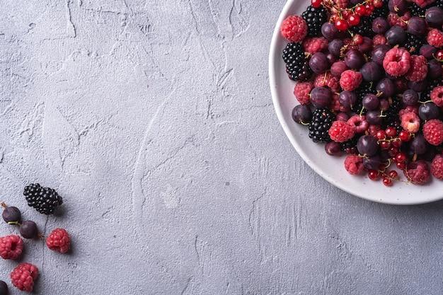 Framboesa madura fresca saborosa, amora, groselha e bagas de groselha vermelha no prato, fruta de comida saudável na mesa de concreto de pedra, espaço de cópia da vista superior