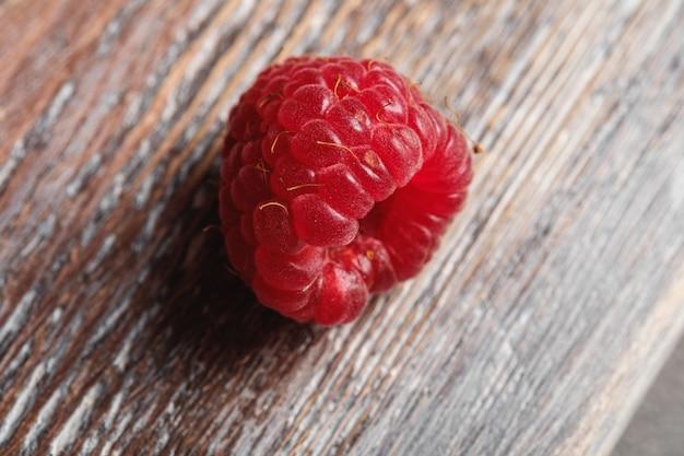 Framboesa na velha tábua de madeira, frutas saudáveis no verão, macro de visão de ângulo