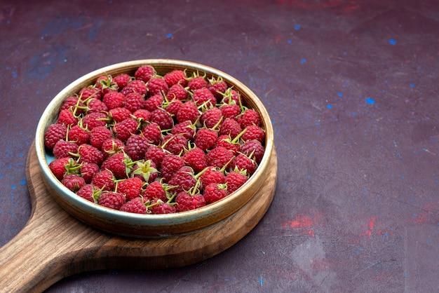 Framboesa vermelha fresca com frutas maduras no fundo azul escuro.
