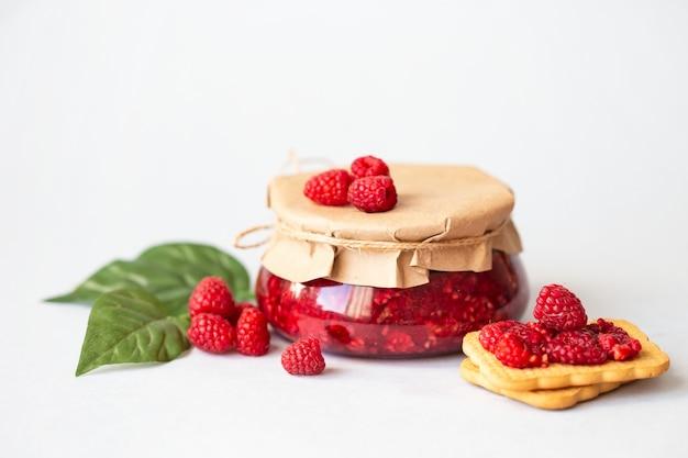 Framboesas com açúcar, framboesas frescas saudáveis, geléia caseira em uma jarra, café da manhã na luz