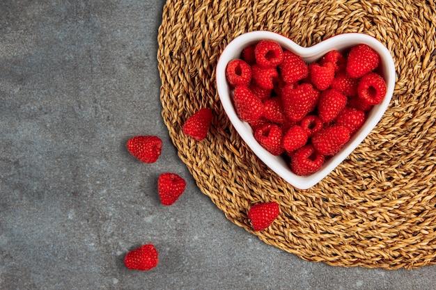 Framboesas de bom gosto em um prato em forma de coração no placemat de vime e fundo cinza asfalto, configuração plana.