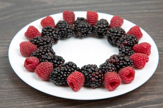 Framboesas e amoras em um prato branco. vitamina e dieta foo