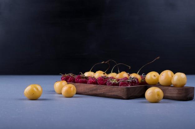 Framboesas e cerejas em uma bandeja de madeira em fundo escuro