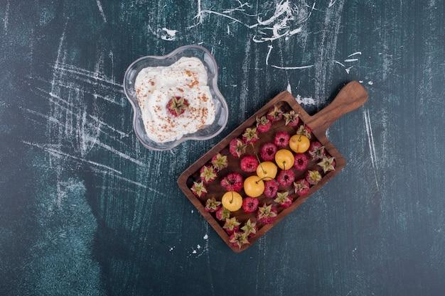 Framboesas e cerejas em uma travessa de madeira com um copo de sorvete no centro