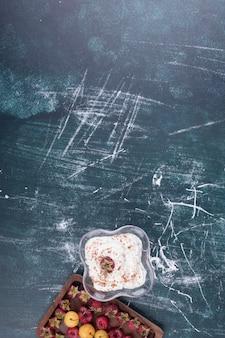 Framboesas e cerejas em uma travessa de madeira com um copo de sorvete