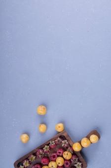 Framboesas e cerejas em uma travessa de madeira