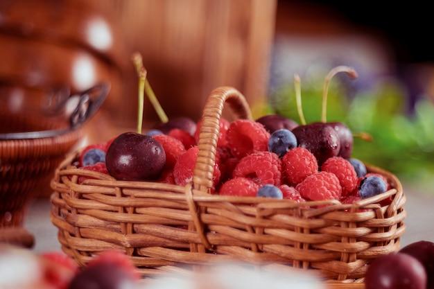 Framboesas e mirtilos em cesta com doce de cereja